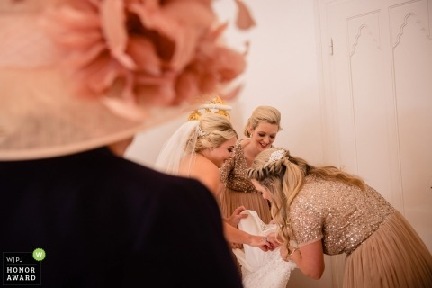 Documentary wedding photo of women helping bride with dress at Budapest