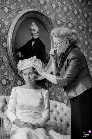 Documentary wedding photograph of bride getting help with veil hat in Zuid Holland