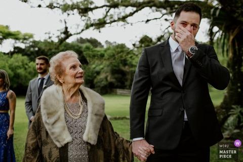 Zdjęcie ślubne pana młodego przejęte przez emocje z Rio Grande do Sul, gdy zakrywa twarz dłonią fotografia ślubna w alto da capela