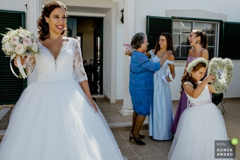 Wedding photo shoot in Santarém - Portugal a bride standing in the sunshine holding her bouquet while hey Young flower girl inspects her heart shaped flower arrangement