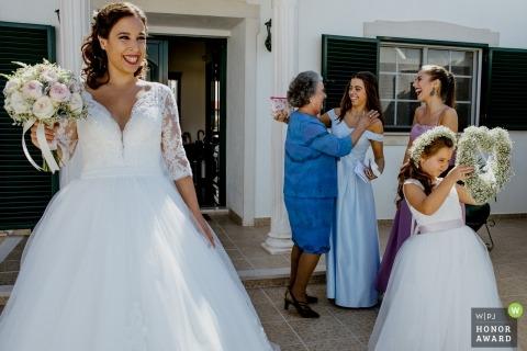 Séance photo de mariage à Santarém - Portugal une épouse debout au soleil tenant son bouquet pendant que héhé Une jeune fille aux fleurs inspecte son arrangement floral en forme de cœur