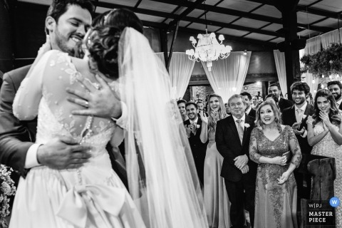 Belo Horizonte  wedding photojournalism image of a couple embracing and smiling on the dance floor during their first dance