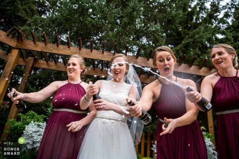 Wedding pictures of wedding party popping champagne - Popping Champagne by Minneapolis photographer