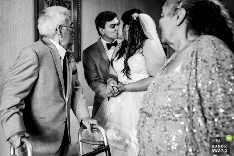 Milwaukee, Wisconsin couple kissing near relatives during their wedding