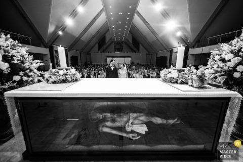 Igreja Nossa Senhora Rainha - Belo Horizonte - Hochzeitsfotojournalismusbild eines Paares innerhalb der Kirche mit Jesus-Figur unter Tabelle