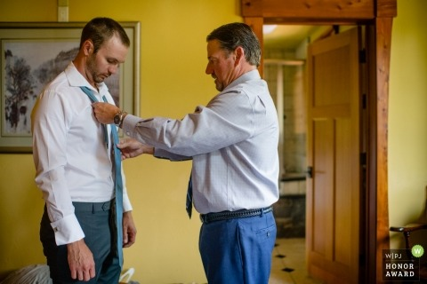 Documentary wedding photography at Lake Tahoe, California - father of the bride helping future son in law put on a tie for the first time ever