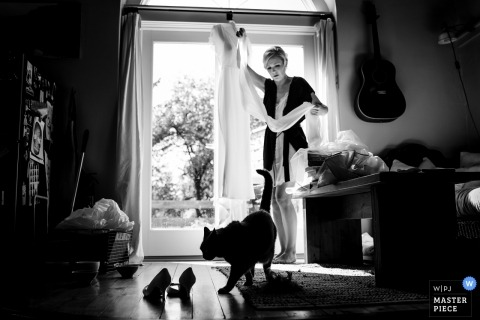 Ferrisburgh, Vermont documentary wedding photo of bride with her hanging dress and a walking cat