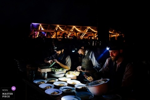 Huwelijksfoto van verkopers die voedsel in dark voorbereiden gebruikend koplampen in Putney, Vermont