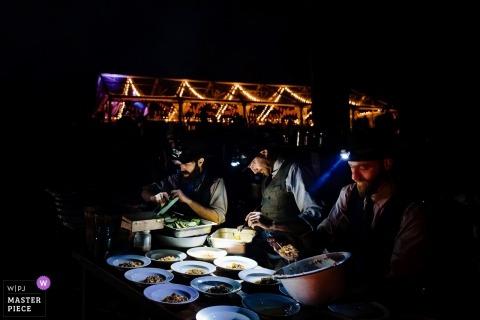 Wedding photo of vendors preparing food in the dark using headlamps in Putney, Vermont
