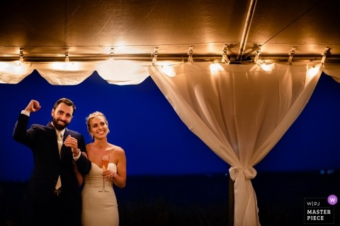Falmouth, Massachusetts  couple during their wedding - groom pumping fist during speeches and toast inside tented wedding