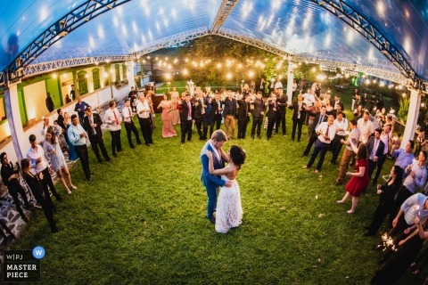 Fazenda Joaguara Velha  wedding photojournalism image of a couple during first dance under clear tent on grass