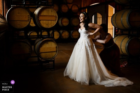 The bride laughs while putting on her dress in the barrell room before her Crooked Willow Farms wedding in Larkspur, Colorado