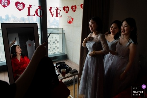 Guangdong documentary wedding photo of bride getting ready in mirror with 3 bridesmaids looking on