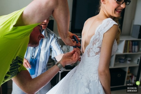 Slowakei-Hochzeitsfotografie einer Braut, welche die Hilfe erhält, die in ihr Kleid kommt