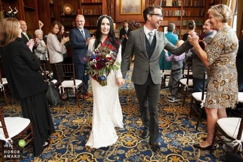 Ślubna fotografia panny młodej i pana młodego wychodzącej z ceremonii weselnej, gdy chwyta dłoń kobiety - małżeństwo Bostonu