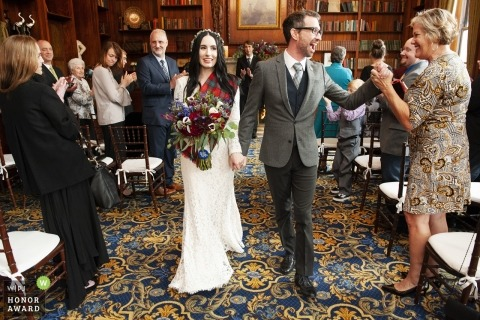 Wedding photograph of the bride and groom exiting the indoor ceremony as he grasps the hand of a female guest - Boston couples getting married