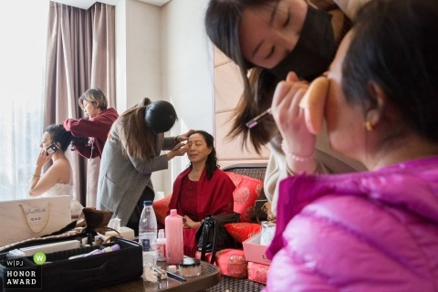 Documentary wedding photograph in Beijing of three separate women having make up put on in a hotel room