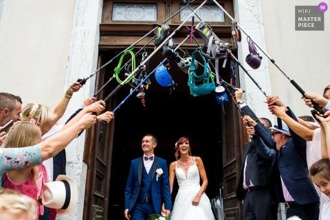 Auvergne-Rhône-Alpes-Hochzeitsfotojournalismusbild eines Paares, welches die Kirche unter einem Handschuh des entspannenden Wanderns und des Kletterns der im Freien verlässt