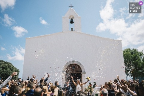 Wedding pictures of bride and groom leaving church under confetti and flower petals by Bari photographer