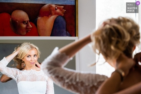 Wedding photo shoot of bride holding her hair while getting into her dress in Kapellen