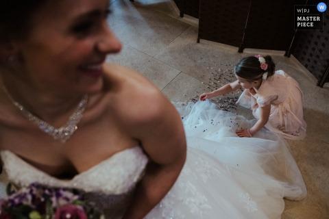 La foto del matrimonio dell'Old Kent Barn della fioraia che fissa l'abito della sposa.