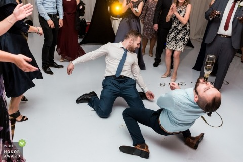 Wedding photojournalism at Toronto | Two male guests drinking and dancing alone