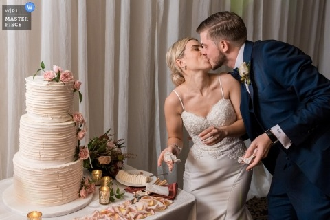 Wedding shoot with Toronto couple kissing at their reception during the cake cutting