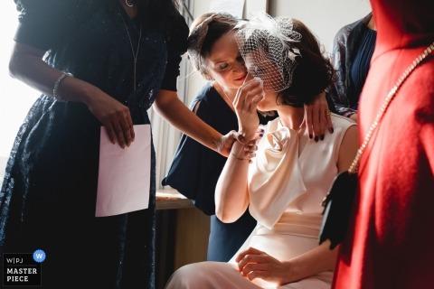Paris-Dokumentar-Hochzeitsfoto der Braut wird getröstet, während sie Tränen abwischt