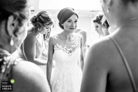 Wedding photo of the brides surrounded by her close friends as she gets dressed for the ceremony in New Jersey