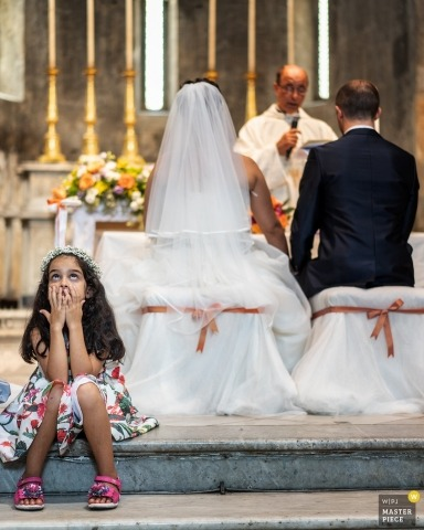 Picture of a couple at the altar by a top Massa and Carrara wedding photographer - girl at ceremony in church