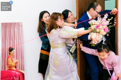 Hochzeitshoot in Fujian eines Bräutigams, der das Tor zusammenstößt, um zu seiner neuen Braut zu gelangen