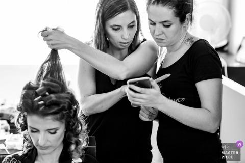 Hochzeitsfotoshooting in Madrid | zwei Frauen, die Telefon benutzen, um mit der Frisur der Braut zu helfen