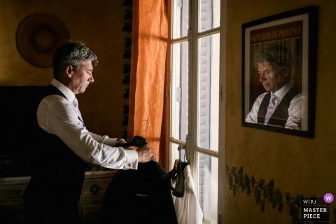 Fotos de boda por el fotógrafo Oppedette, Francia | Preparándose fotografía de boda del novio reflejada en el vidrio de una imagen enmarcada en la pared