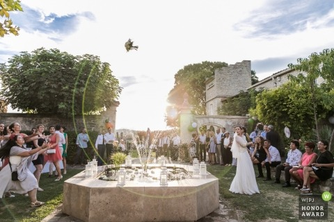 Throwing the bouquet over water fountain | wedding photography in Montpellier, FRANCE