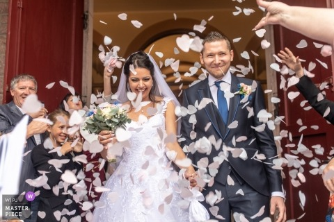 Picture of a couple navigating flower petal shower by a top Mulhouse, France  wedding photographer