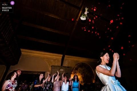 Hochzeitsfotojournalismus Bild in Spanien von der Braut, die den einzelnen weiblichen Gästen an der Rezeption ihren Strauß wirft
