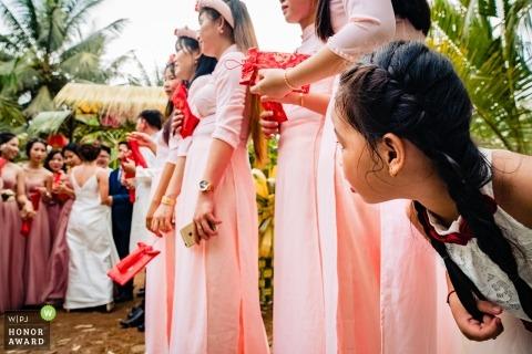 Huwelijksfoto in Ho Chi Minh van een jong bloemmeisje met bruidsmeisjes tijdens een openluchtceremonie
