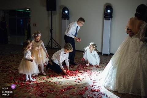 Slovakia wedding photojournalism image of a couple dancing with children picking up flower petals off the dance floor.