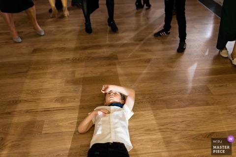 Documentaire huwelijksfoto van jonge jongen die op zijn rug de dansvloer in Polen, Gdansk ligt