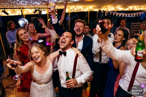 Newlyweds and friends dancing in marquee wine in hand at Macaroni Woods wedding