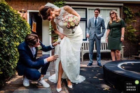Utrecht wedding shoot with a couple working to fix her dress.