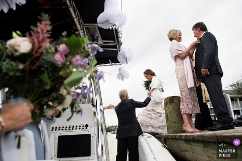 Wedding pictures of bride loading into boat by nantucket, massachusetts photographer