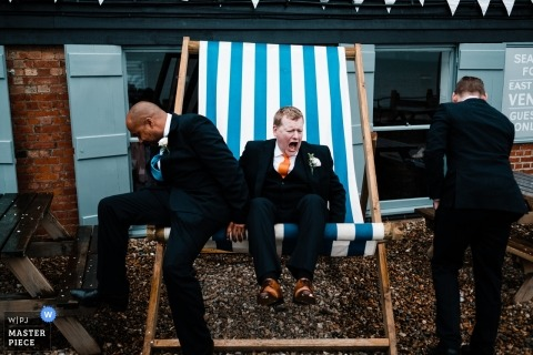 Groom sits on large wet deck chair, during a wet and windy wedding at East Quay Venue