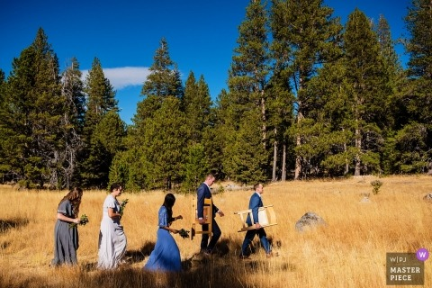 Lake Tahoe wedding photo | wedding photograph of pre-ceremony of guests walking across field carrying chairs