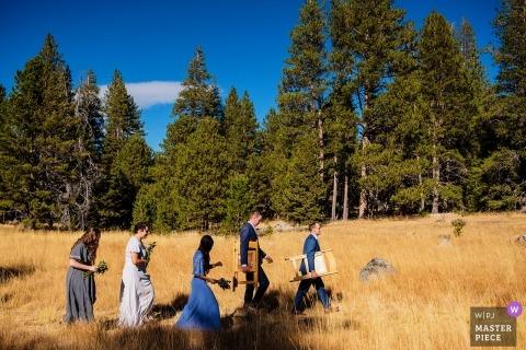 Lake Tahoe Hochzeitsfoto | Hochzeitsfoto der Vorzeremonie von Gästen, die über Feld tragende Stühle gehen