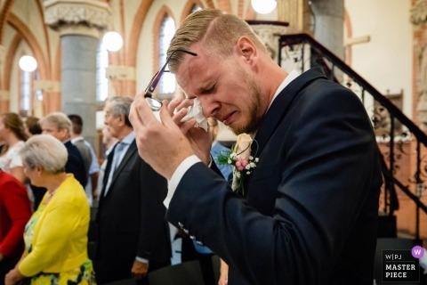 uden Hochzeitsfoto eines Mannes, der Tränen unter seiner Brille abwischt