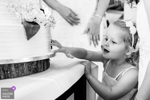 Wedding photojournalism of girl touching wedding cake in rotterdam