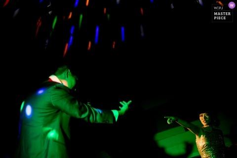 Beeld van een paar dat bij ontvangst onder groene DJ-lichten door een hoogste het huwelijksfotograaf van San Jose danst