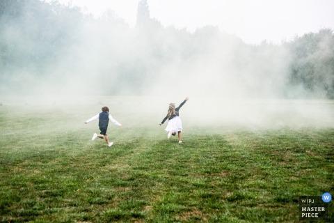 Photo de mariage d'enfants courant dans un champ de fumée par un photographe de Loire-Atlantique