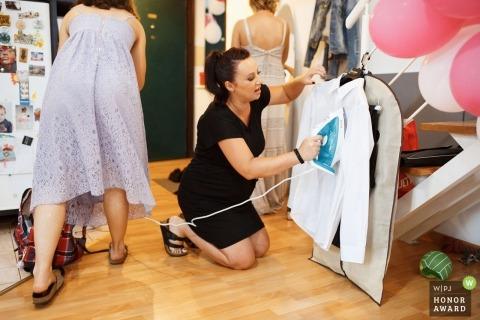 Documentary wedding photograph of woman ironing grooms shirt at Zagreb, Croatia